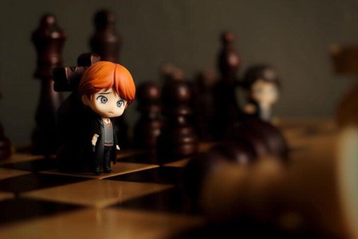 Artista toma fotografías de figuras miniatura de personajes de películas, series y videojuegos; Harry Potter, Ron Weasley en el ajedrez gigante
