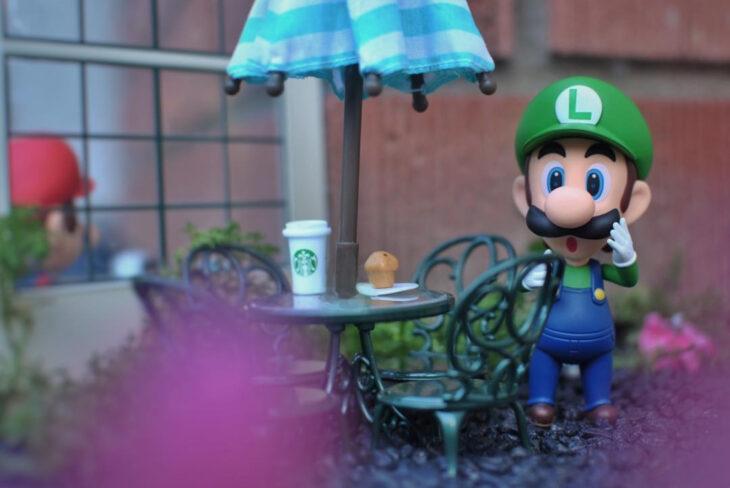 Artista toma fotografías de figuras miniatura de personajes de películas, series y videojuegos; Mario Bros, Luigi en Starbucks
