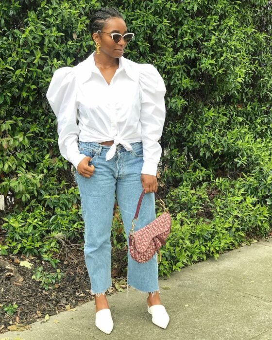 Girl wearing a white button-down shirt with jeans and flats