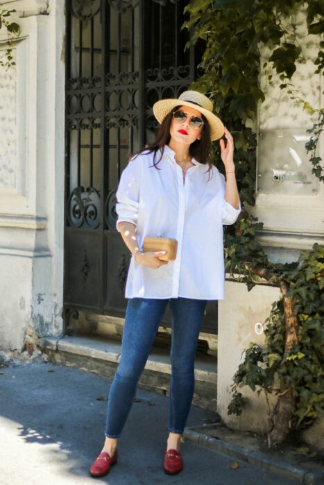 Girl wearing a white shirt with jeans, hat and flats