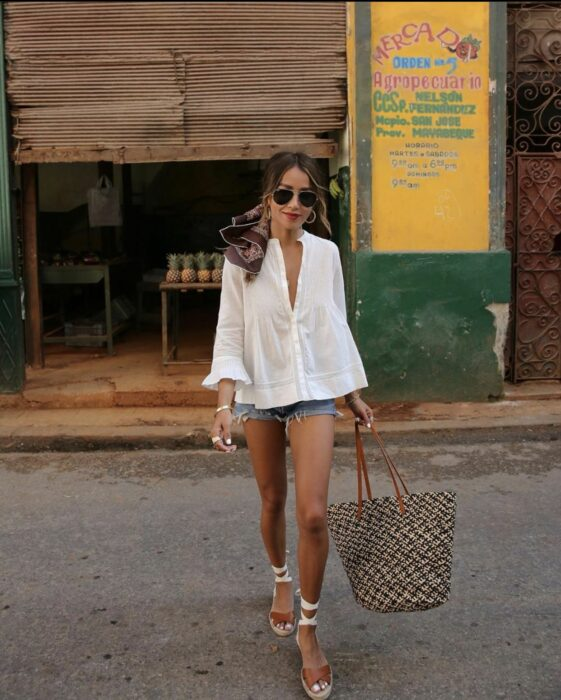 Girl wearing a white button-down shirt with shorts and espadrilles