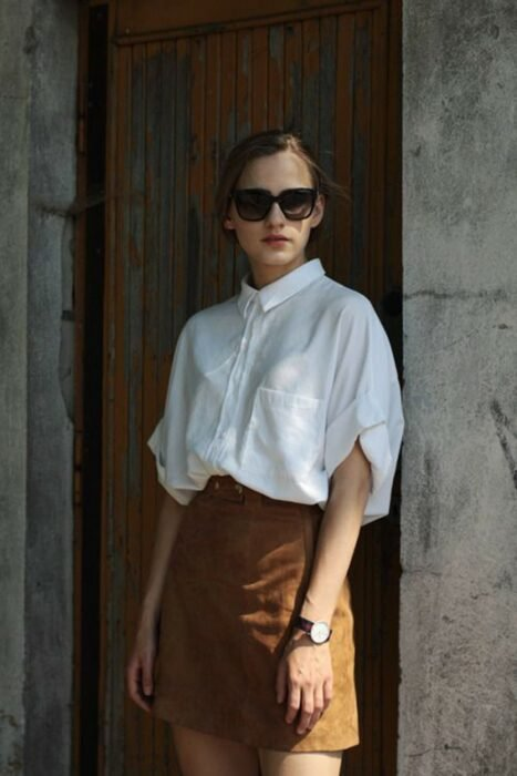 Girl wearing a white shirt along with a brown skirt