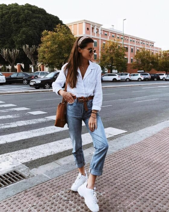 Girl wearing a white button down shirt and jeans along with tennis shoes