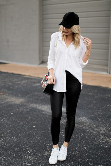 Girl wearing a white shirt along with black leggings and flats