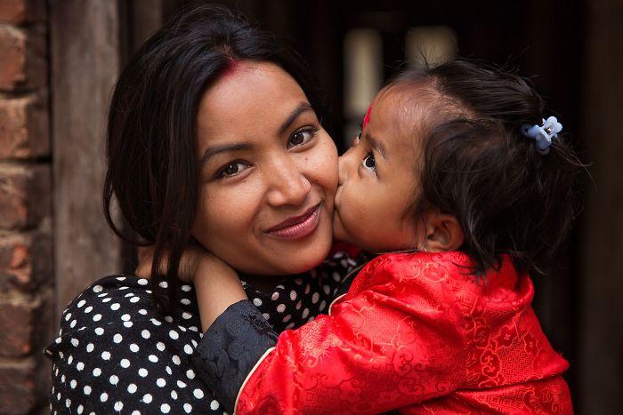 Fotografía de Mihaela Noroc, bebé dando un beso en la mejilla a su mamá