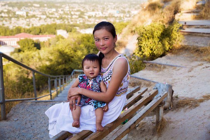 Fotografía de Mihaela Noroc, mujer sosteniendo a su bebé en piernas sentada en un banco de madera