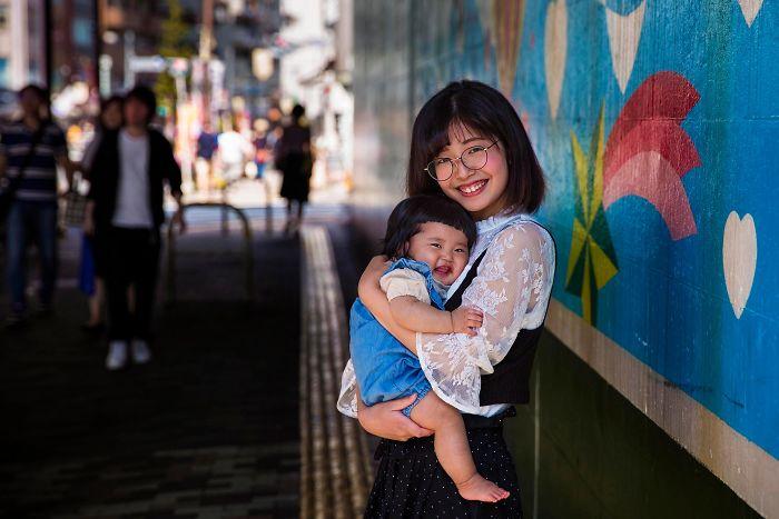 Fotografía de Mihaela Noroc, madre cargando a su hijo en una estación de metro