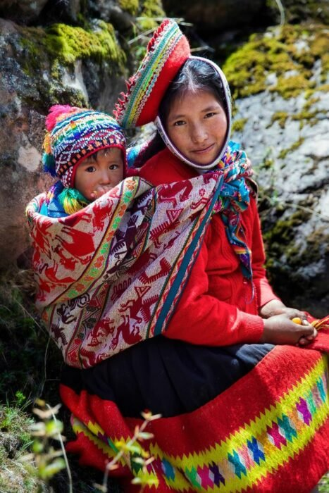 Fotografía de Mihaela Noroc, cargando a su bebé en un reboso