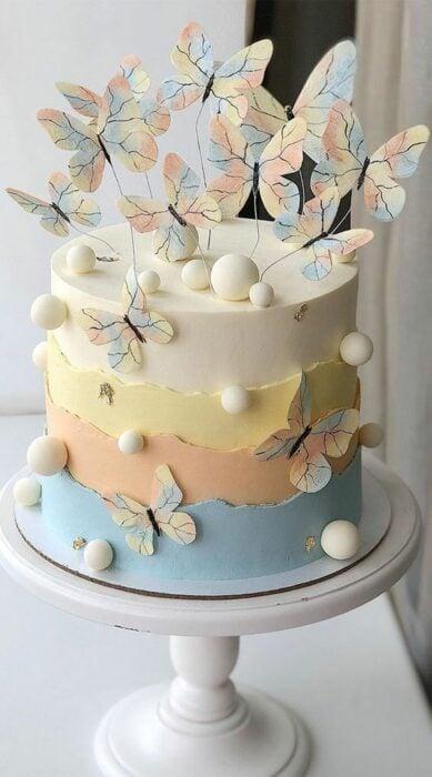 Pastel de sabores decorado con mariposas de tonos tenues; Hermosos pasteles con mariposas