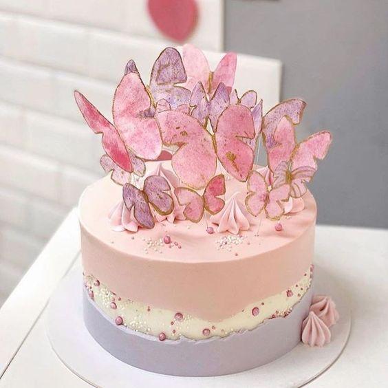 Pastel de zarzamora en colores rosa, balnco y morado decorado con mariposas en tonos rosas; Hermosos pasteles con mariposas