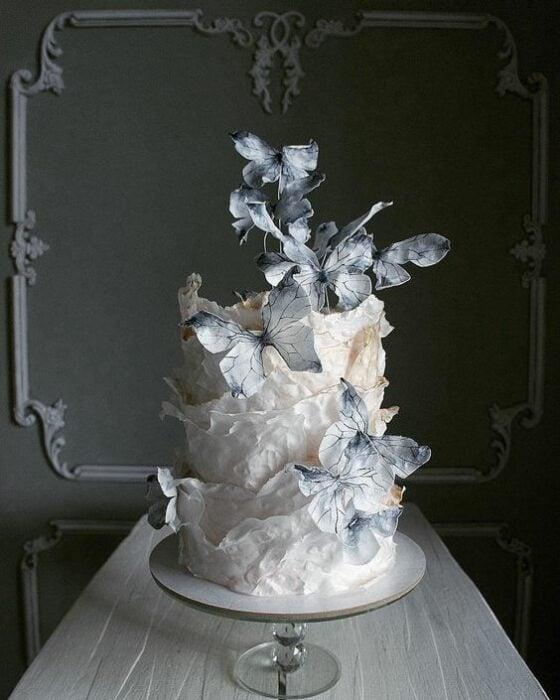 Pastel de bodas de tres pisos con betún de vainilla decorado con mariposas de papel en tonos grises; Hermosos pasteles con mariposas