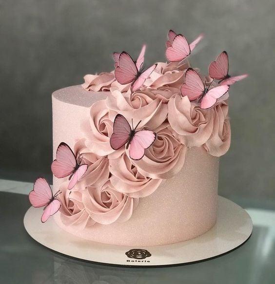 Pastel de fresas con crema en color rosa tenue, decorado con betún en forma de rosas y mariposas; Hermosos pasteles con mariposas