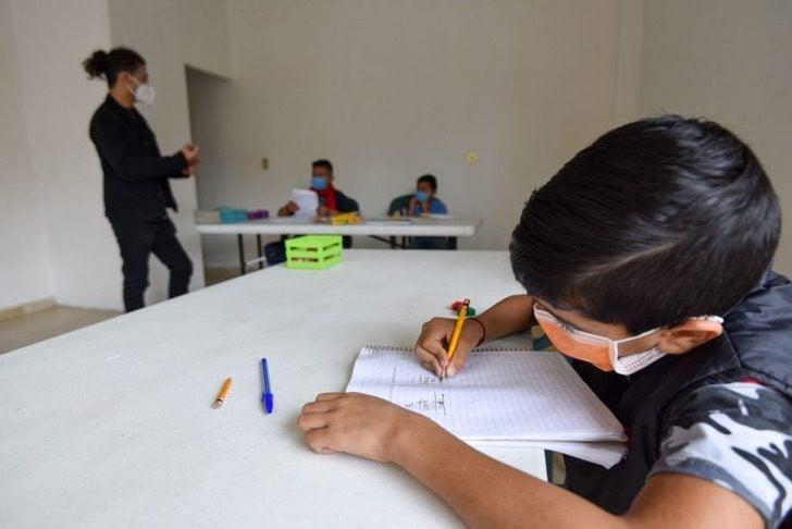 Niño tomando clases en un pequeño salón de clases improvisado