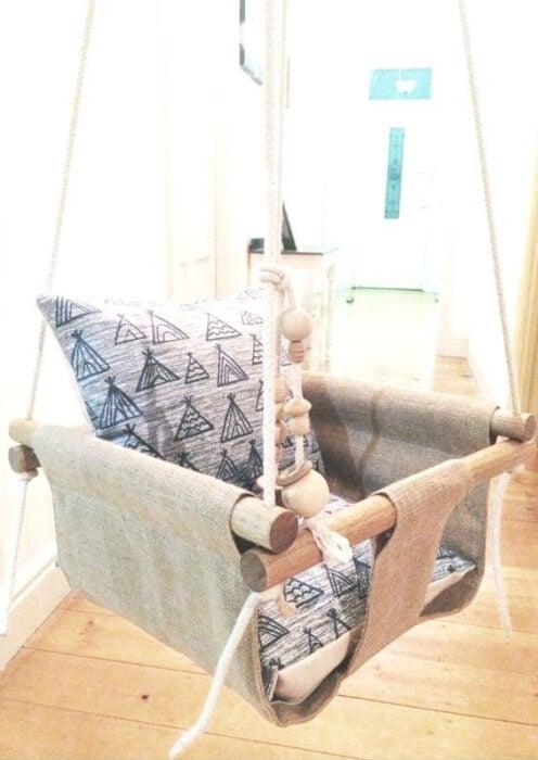 Columpio para bebé sujetado con cuerdas y decorado con diferentes cojines en color azul con blanco