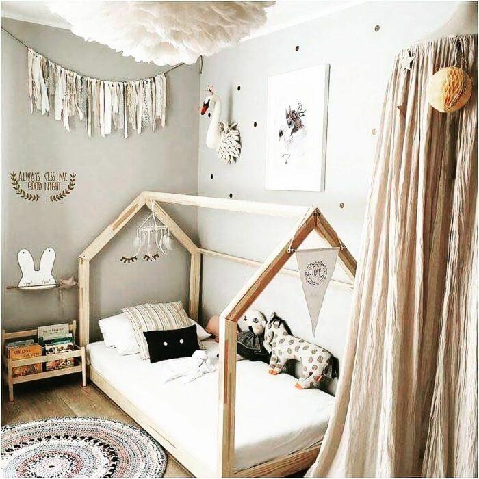 Recamara infantil decorada con un estilo montesori en el que la cama está abajo. Tiene cortinas en color dorado, muebles y un tapete