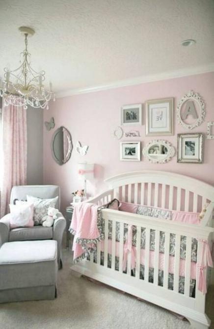 Decoración de la habitación de una bebé en tonos rosa con un sofá en la esquina de color gris y diferentes cuadros sobre la cuna color blanco
