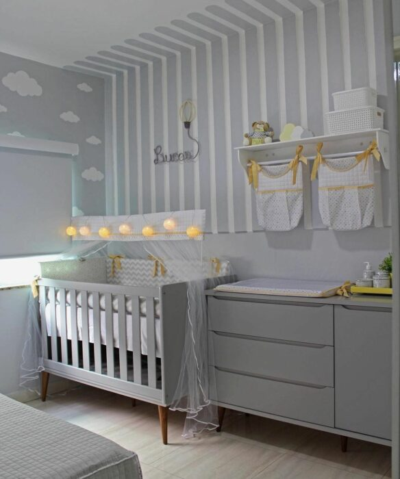 Decoración del cuarto del bebé en tonos color gris con una cuna colocada a un lado de la ventana, cambiador y repisa para los pañales