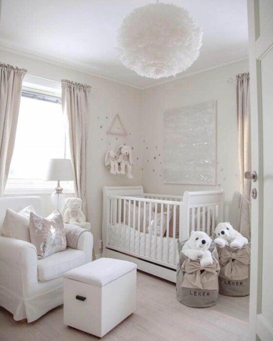 Cuarto de un bebé decorado en color blanco con muebles blancos y una lámpara en forma de pelota