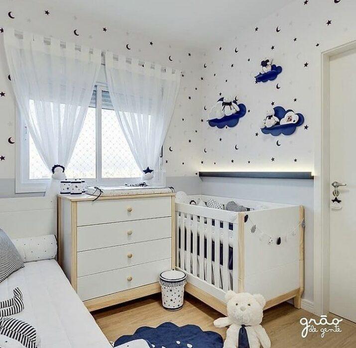 Decoración del cuarto del bebé en tonos azules con blanco con una cama y una cuna separadas por un cambiador en medio de ambas