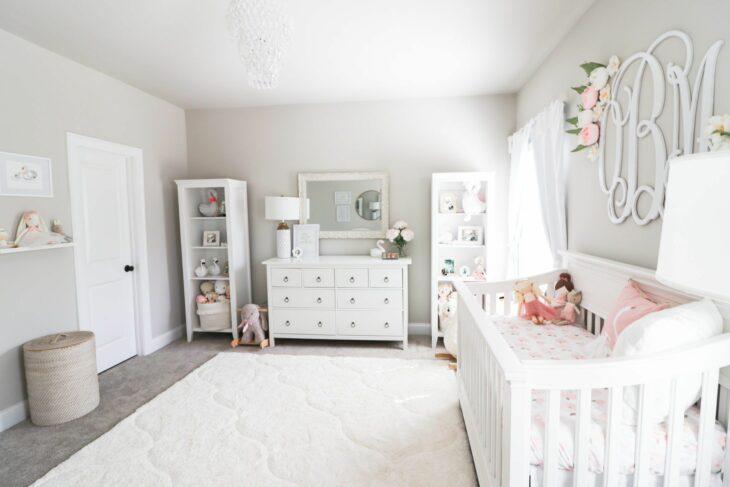 Habitación de un bebé decorada con muebles en color blanco con una cuna, cambiador y una repisa para acomodar juguetes