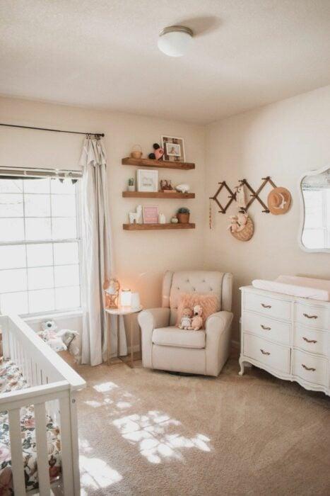 Habitación de un bebé con cuna, sillón para amamantar, repisas de decoración y un cambiador de pañales con varios cajones