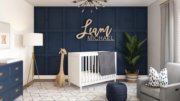 Cuarto del bebé decorado en tonos azul marino con el nombre en una de las paredes del fondo. Cuna de color blanco, jirafas y un sofá en color plateado
