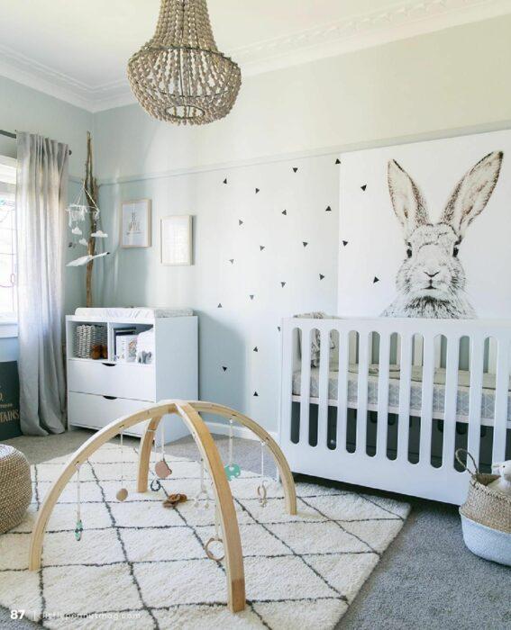 Habitación para un bebé con un móvil de juegos en la alfombra, cuna de color blanca y un cuadro de conejito
