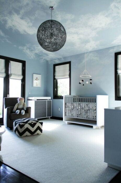 Habitación para un bebé decorada en tonos azules con un sofá, cuna y una lámpara en forma de luna