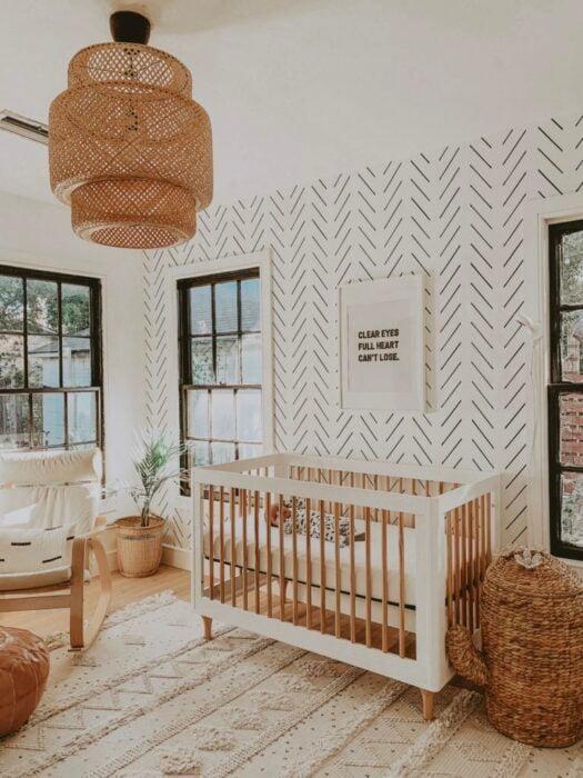 Decoración de la habitación de un bebé en tonos dorados con una cuna de madera de color blanco con café, mesedora y mueble para guardar artículos
