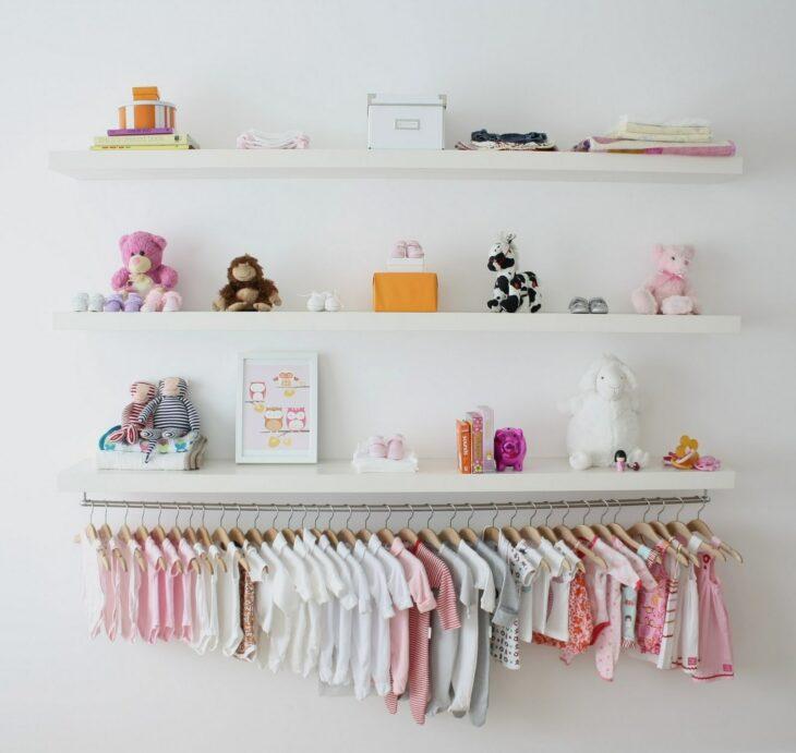 Mini closet usado para colgar la ropa de un bebé, sobre él hay repisas con diferentes juguetes y decoraciones