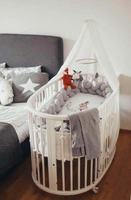 Cuna estilo moises en color blanco colocada a un lado de la cama principal