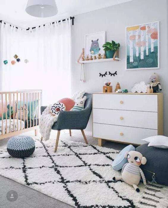 Habitación para un bebé con muebles en color azul, cuna de madera, cajonera de color blanco y diferentes juguetes regados por el lugar