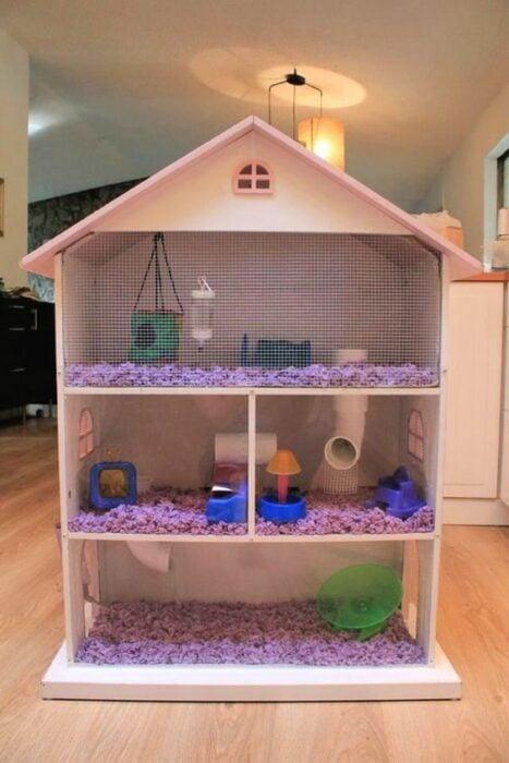 Casita para hámster heche en forma de casita de muñecas con reja blanca y acondicionada con aserrín, tobogán y juguetitos de colores