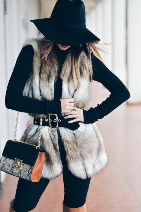 Chica con chaleco en tono blanco con toques beige y sombrero negro a juego; ideas para llevar chaleco durante el otoño-invierno