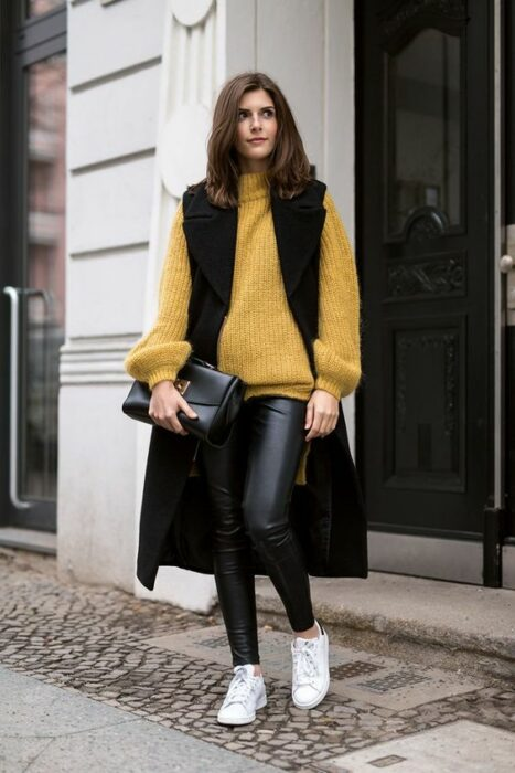 Chica llevando chaleo oversize de gamuza con suéter amarillo; ideas para llevar chaleco durante el otoño-invierno
