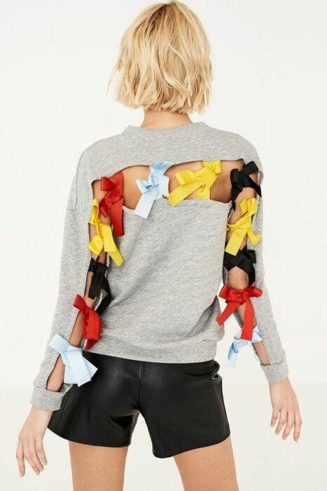 Chica con suéter gris decorado con listones de colores en la espalda