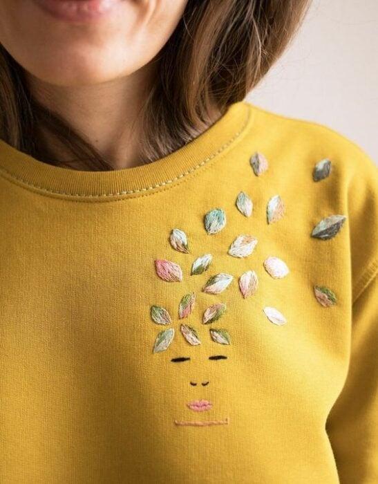 Chica con suéter amarillo bordado al costado