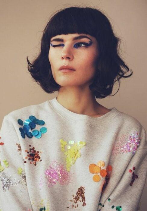 Chica con suéter blanco decorado con lentejuelas