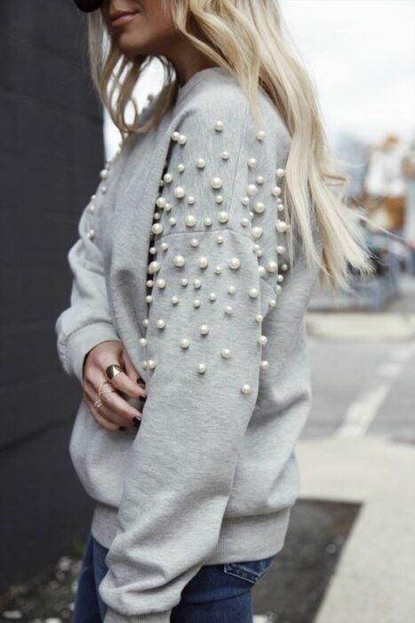 Chica con suéter gris decoraco con perlas