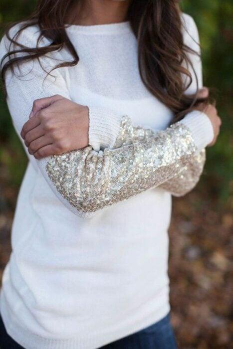 Chica con suéter blanco decorado con lentejuela plateada