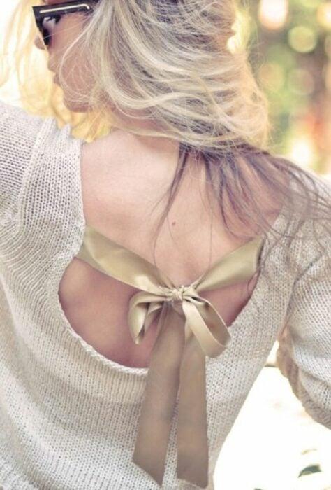 Chica con suéter dorado decorado con listón del mismo color