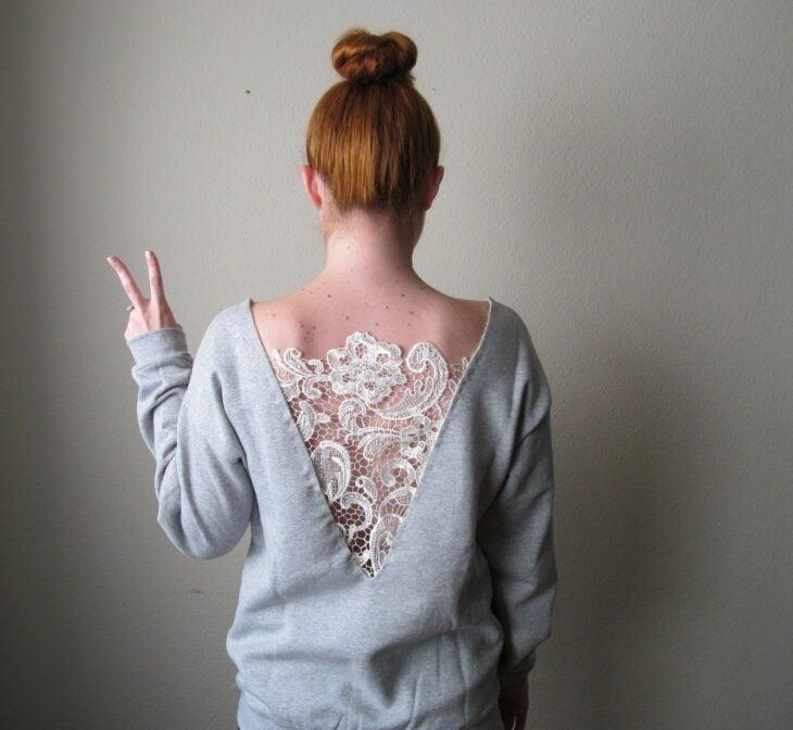 Chica con suéter gris decorado con encaje en la espalda