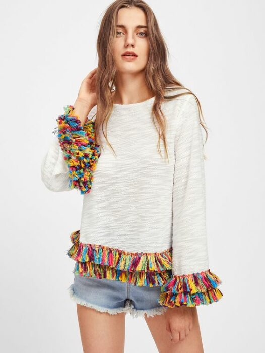 Chica con suéter gris decorado con flequillso de colores
