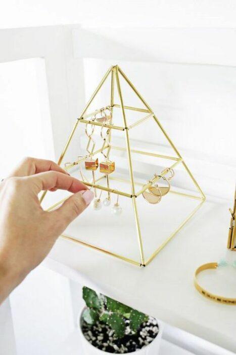 Joyero en forma de pirámide con ciertos niveles y de color dorado