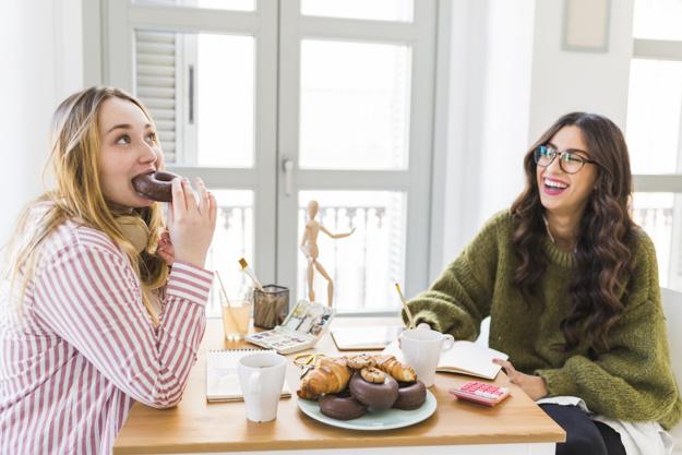 Amigas comiendo donas bañadas de chocolate