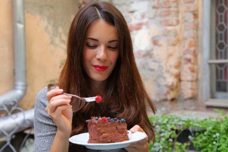Chica comiendo pastel de chocolate con frutos rojos