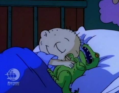 Tommy Pickles dormido mientras abraza a su muñeco Reptar