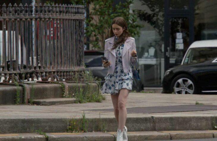 Lily Collins usando un atuendo de vestido floral con chaqueta de color morado con botas blancas en la serie Emily In Paris