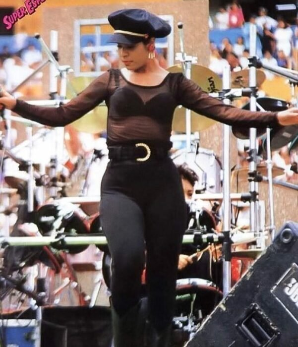 Selena Quintanilla wearing an all black outfit with a black beret beret