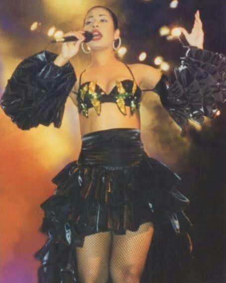 Selana Quintanilla during a concert wearing a ruffled skirt with a crop top with gold details